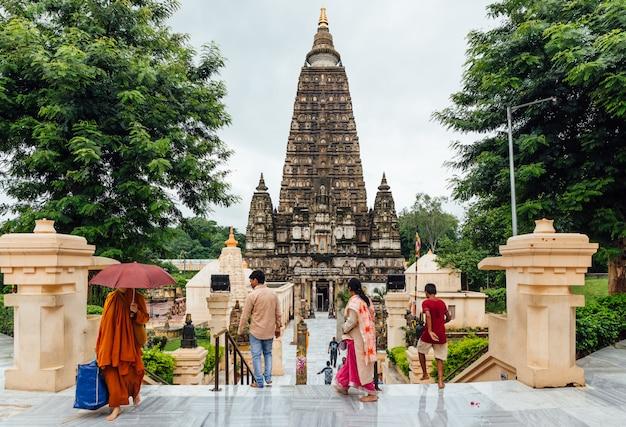 Indische leute, die barfuß zum mahabodhi-tempel für das beten und den pilger beim regnen bei bodh gaya, bihar, indien gehen Premium Fotos
