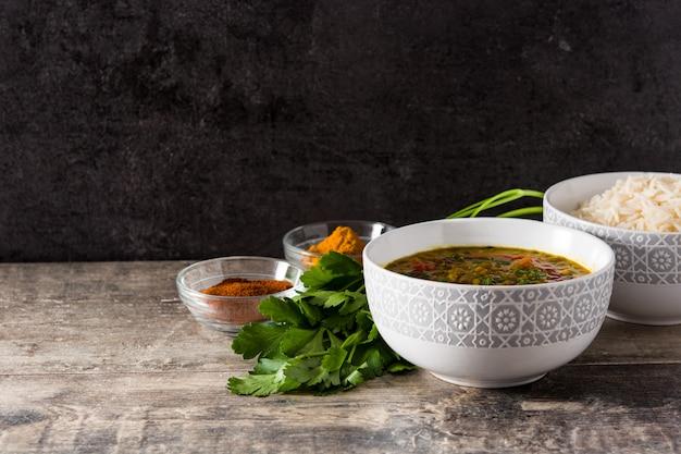 Indische linsensuppe dal (dal) in einer schüssel und in einem basmatireis auf holztisch. kopieren sie platz Premium Fotos