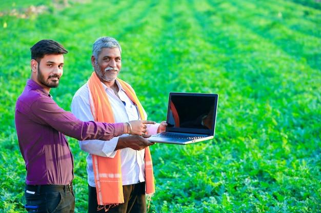 Indischer agronom mit landwirt am feld Premium Fotos
