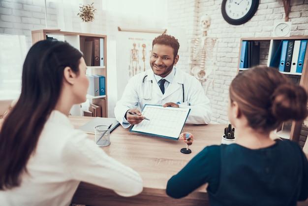 Indischer doktor, der patienten im büro sieht. Premium Fotos
