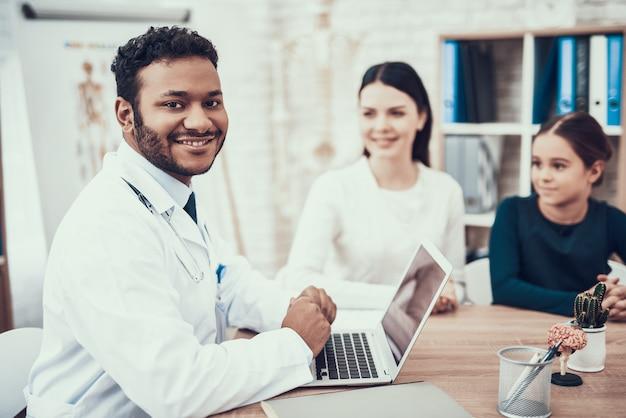 Indischer doktor im weißen kleid, das patienten im büro sieht Premium Fotos