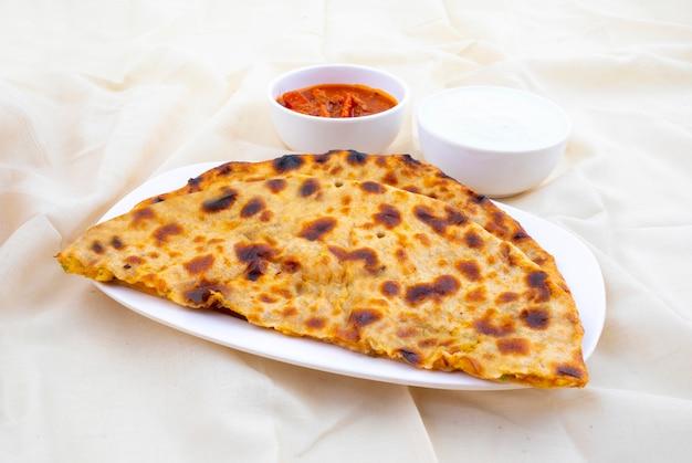Indischer frühstücksteller aloo paratha diente mit klumpen und essiggurke Premium Fotos