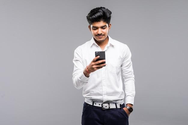 Indischer geschäftsmann, der smartphone mit weißer wand verwendet Kostenlose Fotos