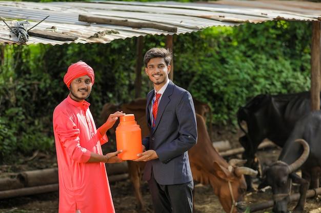 Indischer landwirt und tierhaltungsoffizier, der milchflasche auf milchfarm hält Premium Fotos