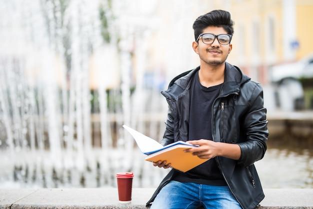 Indischer studentenmann, der einen stapel bücher hält, der nahe brunnen auf der straße sitzt Kostenlose Fotos