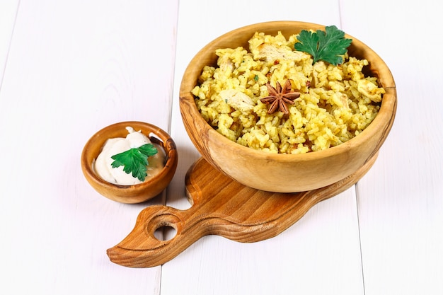 Indisches biryani mit huhn, joghurt, gewürzplatte auf einem holztisch. silvester, weihnachtsgericht. Premium Fotos