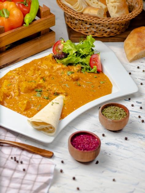 Indisches curry mit hähnchenbrust und tomatensauce, serviert mit lavash. Kostenlose Fotos