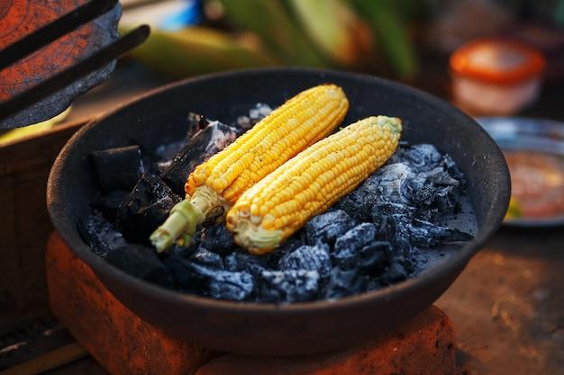 Indisches essen am strand - frische maiskolben werden auf den kohlen geröstet. Premium Fotos