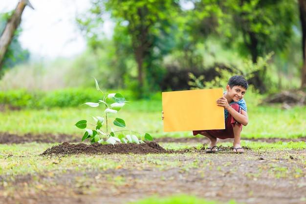 Indisches kind, das leeres plakat hält Premium Fotos