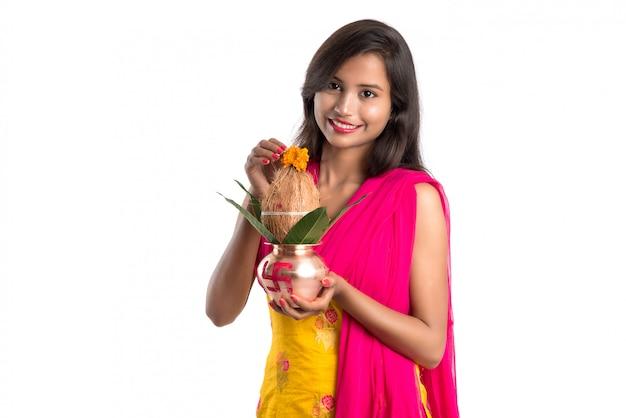 Indisches mädchen, das ein traditionelles kupfernes kalash, ein indisches festival, ein kupfernes kalash mit kokosnuss und ein mangoblatt mit der blumendekoration, wesentlich in hinduistischem pooja hält. Premium Fotos