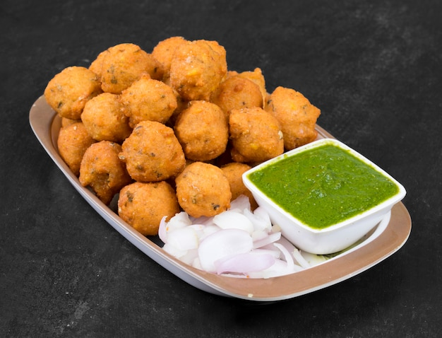 Indisches würziges straßenlebensmittel dal vada auf schwarzem hintergrund Premium Fotos
