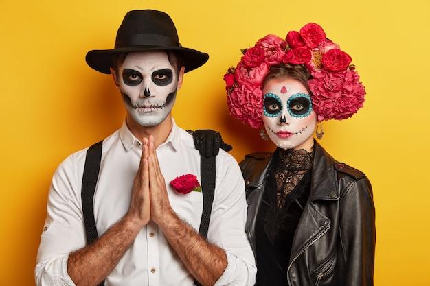 Indoor-foto von betenden gruseligen mann hat bild von zombie, hält handflächen zusammengedrückt, ernsthafte frau mit blumenkranz um den kopf steht in der nähe, hat gruseliges make-up. halloween oder allerseelen tag. Kostenlose Fotos