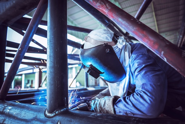 Industriearbeiter am fabrikschweißen, stahlrohrstruktur schweißend Premium Fotos