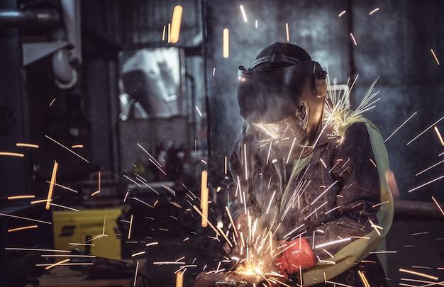 Industriearbeiterarbeiter an der fabrik, die stahlkonstruktion schweißt Premium Fotos