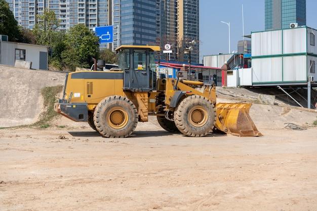 Industriegebäudebaustelle-minibulldozer, die boden während des landstraßengebäudes planiert und bewegt Premium Fotos