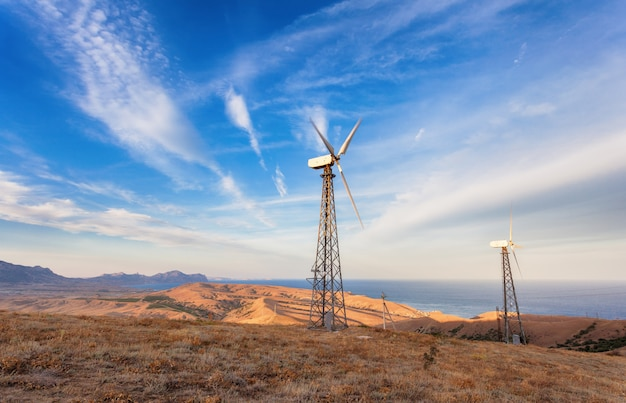 Industrielandschaft mit windkraftanlage, die strom in den bergen bei sonnenuntergang erzeugt Premium Fotos