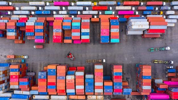 Industrieller behälterkasten der vogelperspektive vom frachtfrachtschiff für import und export in versandyard mit frachtbehälterstapel. Premium Fotos