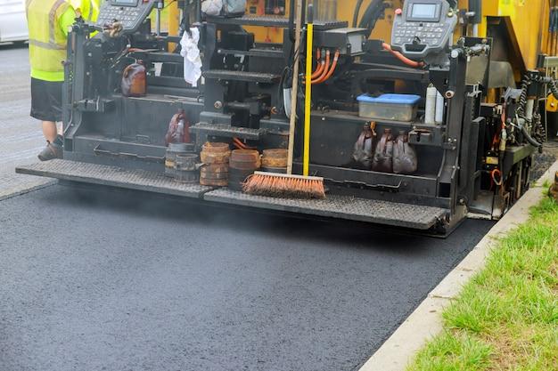 Industrieller pflasterwagen, der frischen asphalt auf baustelle legt Premium Fotos