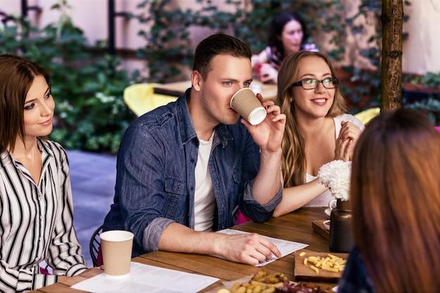 Informelle, freundliche party mit arbeitskollegen im gemütlichen café mit köstlichen snacks an warmen sommertagen Kostenlose Fotos