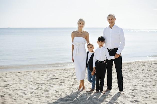 Informelles familienporträt am sandstrand am sonnigen sommertag von eltern und zwei söhnen in formeller kleidung Kostenlose Fotos