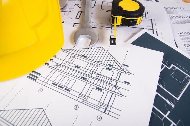 Ingenieur Arbeitsplatz mit Blaupausen, Winkelmesser und Schutzhelm. Kostenlose Fotos
