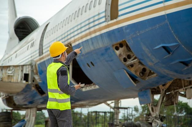Ingenieur, der altes flugzeug für wartung ein flugzeug betrachtet, führen reparaturen durch. Premium Fotos