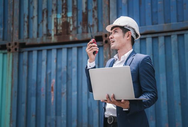 Ingenieur, der auf dem baucontainerhof, dem industriecontainerhof für den import und export für unternehmen arbeitet, vorarbeiter, der das industriecontainerfrachtschiff in der industriezone kontrolliert Premium Fotos