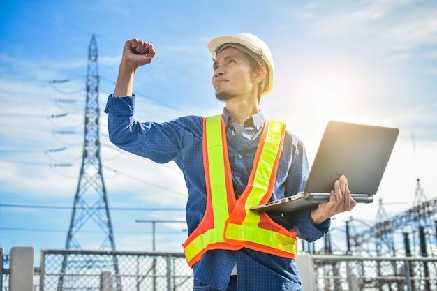 Ingenieur, der computernotizbuch oder laptop und ein kraftwerk mit dem industrietechnologiekonzept der elektrizitätsbehörde hält Premium Fotos