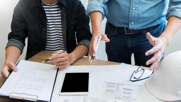 Ingenieur, der das treffen arbeitet an dem planprojekt architektonisch an der baustelle bespricht. Premium Fotos