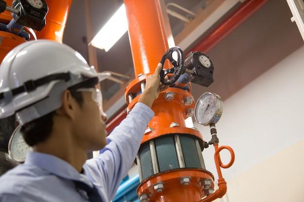 Ingenieur, der kondensator-wasserpumpe und -manometer überprüft Premium Fotos