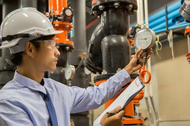 Ingenieur, der kondensatorwasserpumpe und -manometer, kühlerwasserpumpe mit manometer überprüft. Premium Fotos