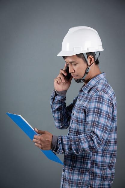 Ingenieur, der pläne hält und anmerkungen über klemmbrett bei der stellung auf grauem hintergrund liest. Kostenlose Fotos