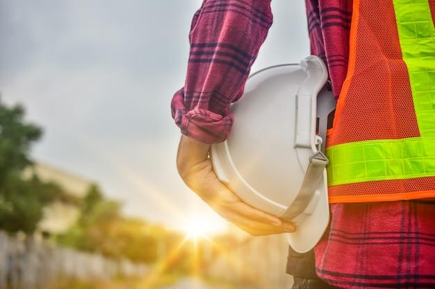Ingenieur, der schutzhelmbauarbeiterberufssicherheitsarbeitsindustriegebäude-personenmanagerservice hält Premium Fotos