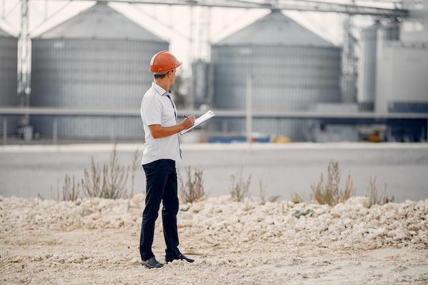 Ingenieur in einem helm, der zur fabrik steht Kostenlose Fotos