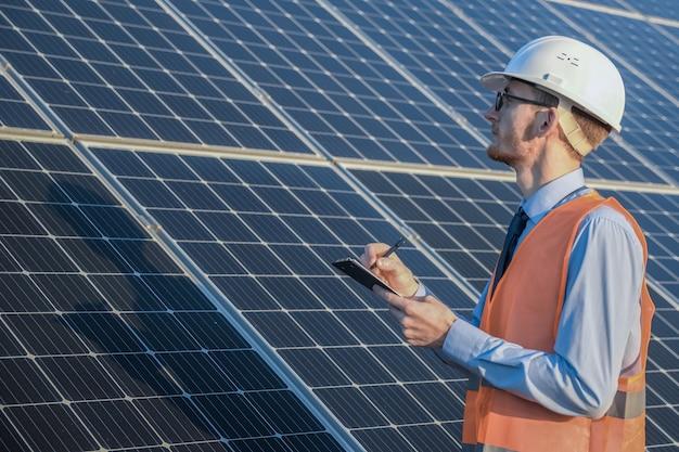 Ingenieur in uniform stehend auf einem der sonnenkollektoren Premium Fotos
