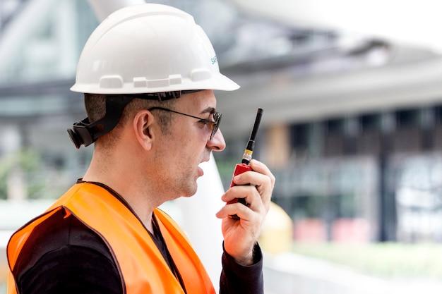 Ingenieur trägt weiße helme und schutzanzug spricht auf funk mit kollegen draußen Premium Fotos