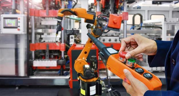 Ingenieur überprüfen und steuern modernen automatisierungsschweißensroboterarm der hohen qualität an industriellem Premium Fotos