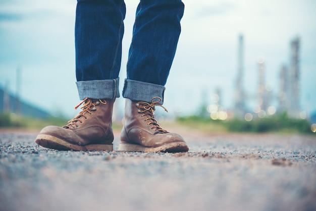Ingenieur wear jeans und braune stiefel für arbeitnehmersicherheit auf hintergrund der raffinerie Premium Fotos