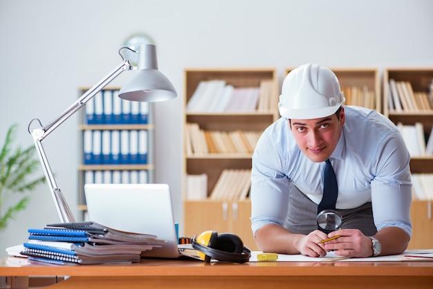 Ingenieuraufsichtsbeamter, der an zeichnungen im büro arbeitet Premium Fotos