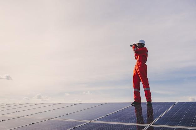 Ingenieure, die sonnenkollektoren bei der stromerzeugung des sonnenkraftwerks reparieren; techniker in industrieuniform auf ebene der berufsbeschreibung bei industrie Premium Fotos