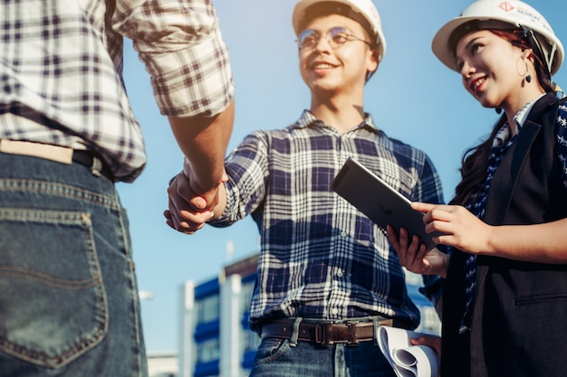 Ingenieure geben sich zusammen mit der sekretärin an der seite die hand. Premium Fotos