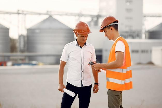 Ingenieure in einem helm, der zur fabrik steht Kostenlose Fotos