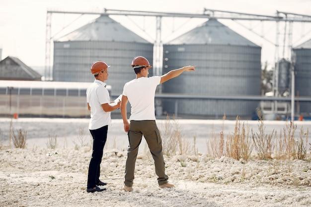 Ingenieure in helmen, die zur fabrik stehen Kostenlose Fotos