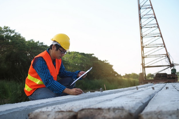 Ingenieure überprüfen die pfähle im baubereich und auf der rückseite befinden sich kräne. Premium Fotos