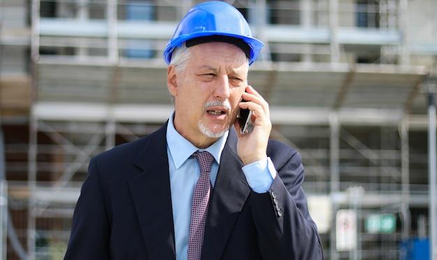 Ingenieurerbauer an der baustelle sprechend am telefon Premium Fotos