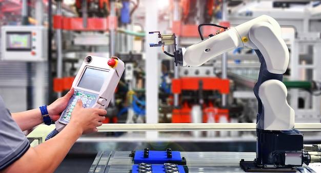 Ingenieurprüfungs- und -steuerungsautomatisierung roboterarmmaschine für automobillager-verpackungsprozess in der fabrik. Premium Fotos