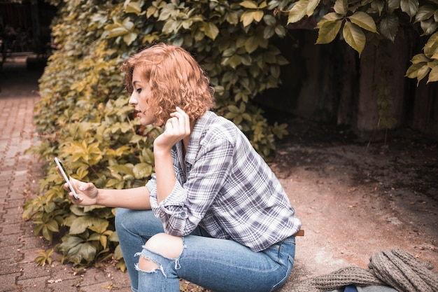Ingwerfrau mit telefon auf straße mit büschen Kostenlose Fotos