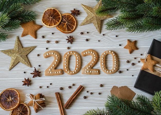 Ingwerkekse in form von zahlen und 2020 neues jahr ingwer kekse aus weißem holz. ansicht von oben. saisonale verpackung, gewürze und silvesterattribute Premium Fotos
