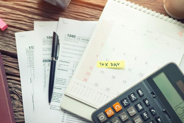 Inkasso- und steuertag mit termin kalender erinnerungsschein steuerformular 1040 mit taschenrechner. Premium Fotos