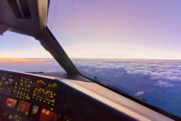 Innenansichtcockpit am copilotsitz, wenn flugzeug in großer höhe über den wolken im himmel fliegt Premium Fotos